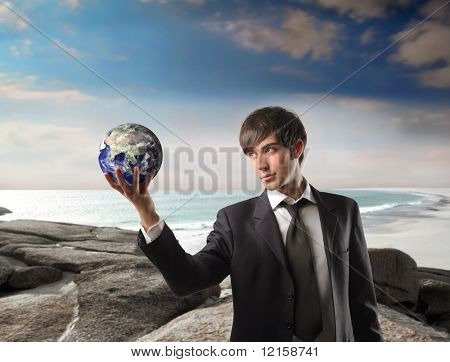 Portrait of a businessman holding a globe in his hands with seascape on the background