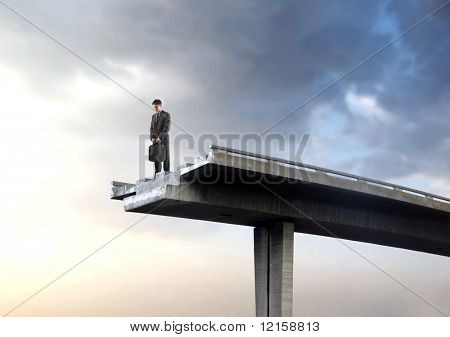 Portrait of a businessman standing on an interrupted highway bridge and looking into the empty space underneath