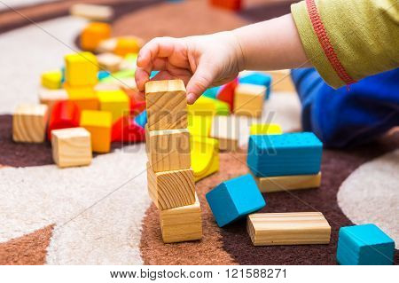 Small Child Playing With Wooden Blocks