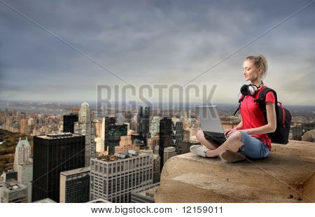 Portrait of a woman sitting on the top of a skyscraper with cityscape on the background