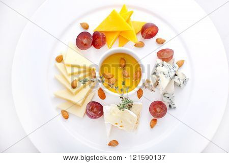 Dish with four kinds of cheese, grapes
