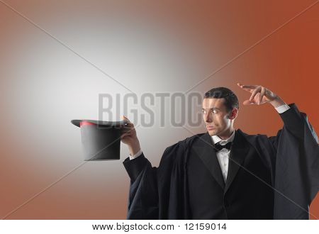 Portrait of a magician casting a spell at his magic hat