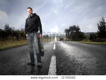 Portrait of a man standing on a countryside road with a skateboard in his hand