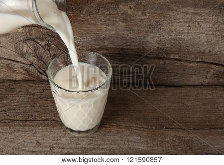 pouring milk from a carafe into the glass on the wooden background close-up