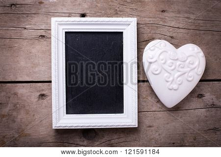 White  Heart And Empty Blackboard On Aged Wooden Background.