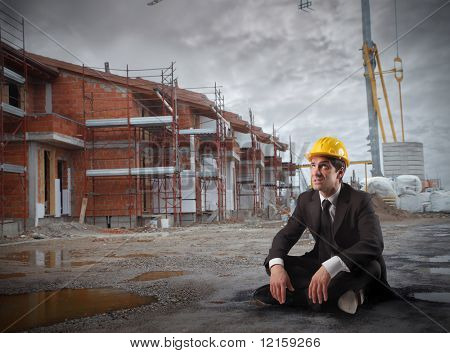 Portrait of a businessman wearing a helmet and sitting in a construction site