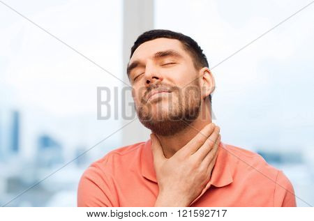 people, healthcare and problem concept - unhappy man touching her neck and suffering from throat pain at home