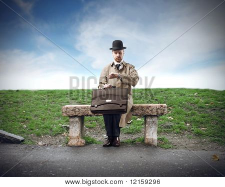 Portrait of a businessman sitting on a bench and looking at his watch