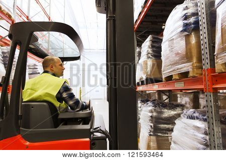 wholesale, logistic, loading, shipment and people concept - man or loader operating forklift loader at warehouse