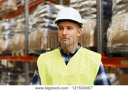 wholesale, logistic, people and export concept - man in reflective safety vest and hardhat at warehouse