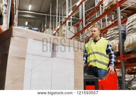 wholesale, logistic, loading, shipment and people concept - man on forklift loader loading boxes at warehouse