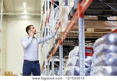 wholesale, logistic, business, export and people concept - serious businessman calling on smartphone at warehouse