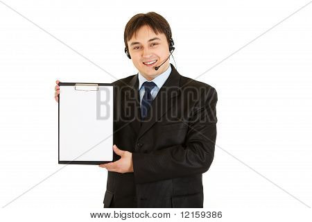 Smiling young businessman with headset holding blank clipboard isolated on white