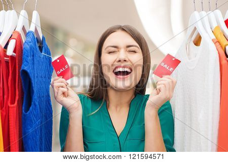 clothing, fashion, sale and people concept - happy woman showing tags on clothes at shopping center or mall