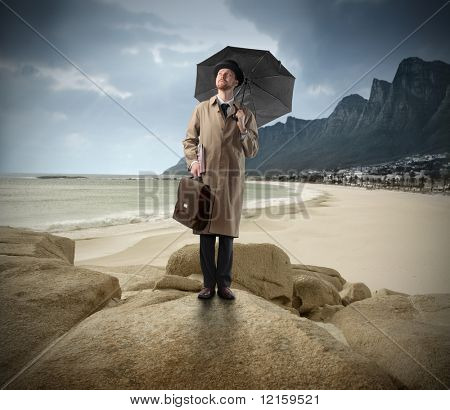 Gentleman with umbrella standing on a rock looking over a seascape