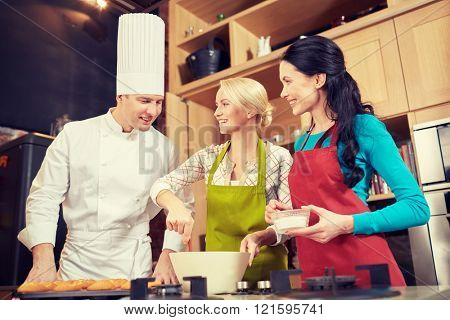 cooking class, culinary, bakery, food and people concept - happy group of women and male chef cook baking muffins in kitchen