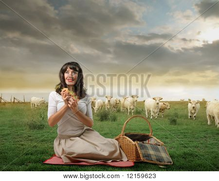 Woman on green meadow having picnic