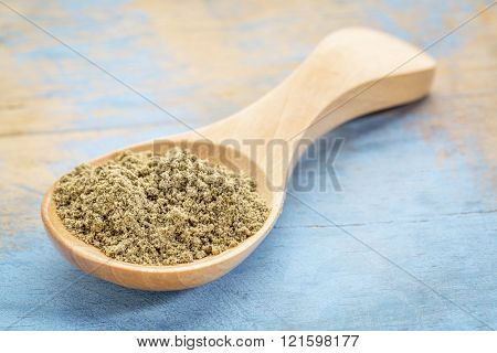 hemp seed protein powder on a wooden spoon against blue painted grunge wood