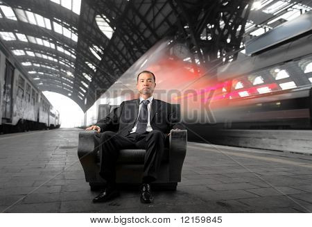 Japanese businessman sitting on an armchair with a train station on the background