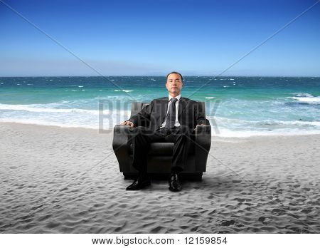 Japanese businessman sitting on an armchair at the beach