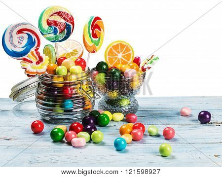 multicolored lollipops candy and chewing gum in glass jar on a white background