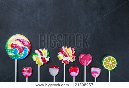 multicolored lollipops candy and chewing gum on a black background.