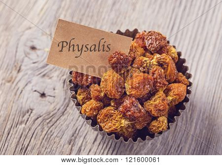 Physalis berries in a bowl on a wooden background