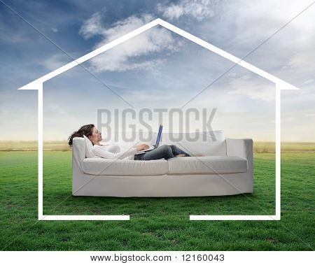 Woman lying on a couch on a green meadow and working on a laptop