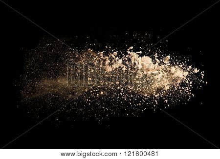 Explosion of brown powder on black background