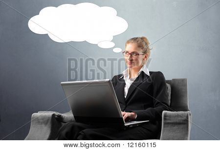 Businesswoman sitting on an armchair with a laptop and thinking