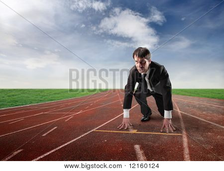 Businessman kneeling on the starting grid of a running track