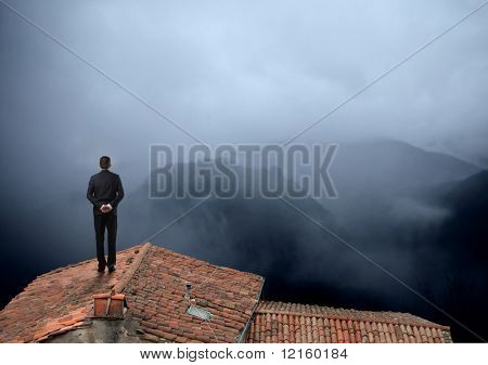 Businessman standing on a rooftop looking over a foggy landscape