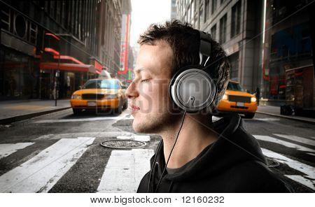 Joven escucha música en una calle de la ciudad