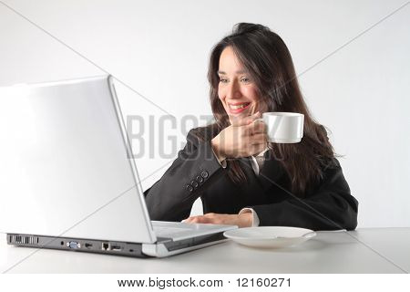 Smiling businesswoman sitting in front of a laptop with a coffee cup in her hands