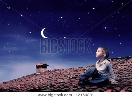 Child sitting on a rooftop and looking at the moon