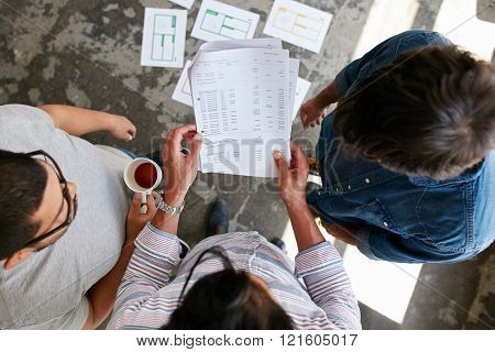 Young People Going Through Financial Documents In Office