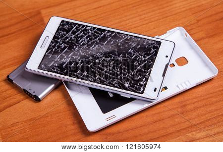 Opened Broken White Mobile Phone With Battery On Wood Ground