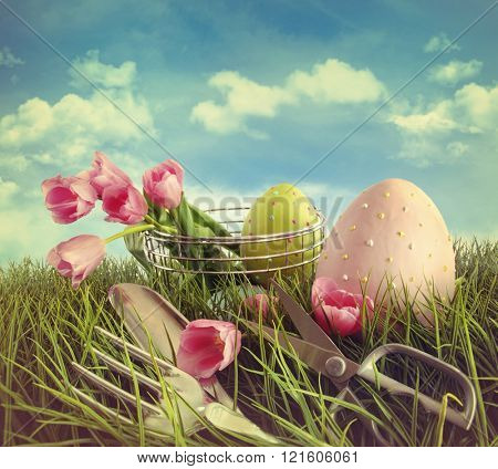 Tulips garden tools and easter eggs in field with blue sky