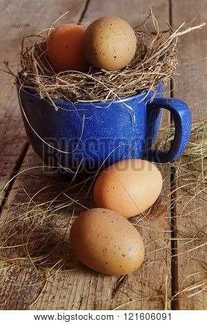 Farm eggs in blue enamel cup with straw