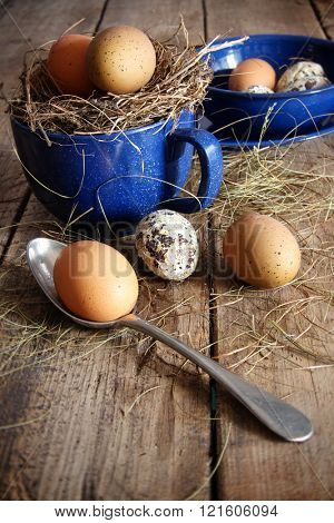 Farm eggs in blue enamel cup and spoon with straw