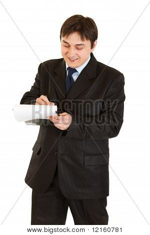 Smiling young businessman making notes in document isolated on white
