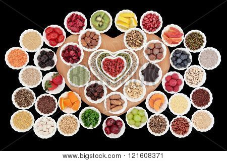 Superfood collection in heart shaped and round porcelain  bowls over black background. High in vitamins and antioxidants.