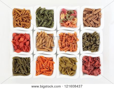 Coloured italian pasta collection in china dishes over white background with spinach, carrot, tomato and durum wheat colouring.