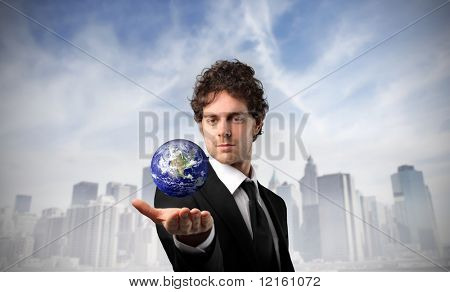 Businessman holding the earth in his hand with cityscape on the background