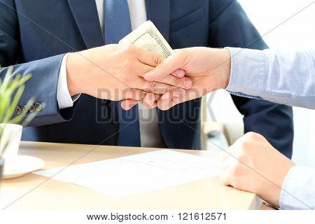 Handshake of businessmen with money.  Bribe. White background behind.