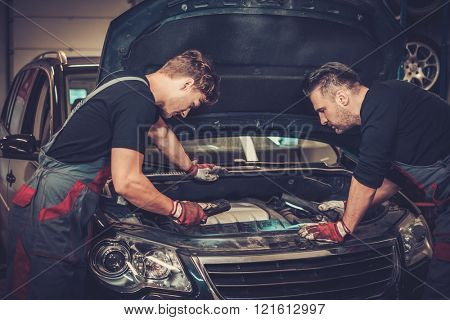 Professional car mechanics checking under hood in auto repair service.