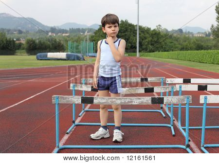 Child standing on a running track full of obstacles