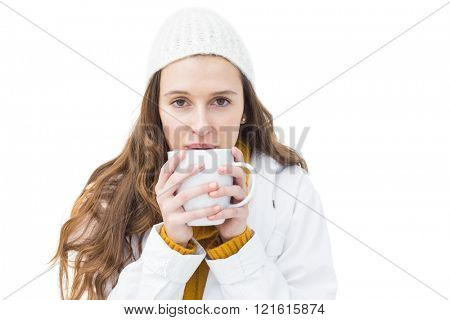 Pretty woman in winter clothes drinking a hot beverage on white background