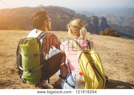 Back view of a young man and woman wanderers are resting after hiking in mountains during their summer adventure male and female backpackers are enjoying wonderful views during their trip overseas