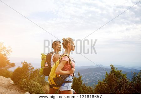 Young beautiful woman and man travelers are enjoying hike and beauty nature view during rest in the fresh air two wanderers are taking break between walking in mountains during their summer adventure